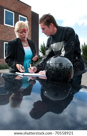 Motorist and a female driver discussing an insurance form after a  collision between a motor and an vehicle - stock photo