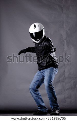 motorist with a helmet, leather jacket and jeans, on grunge background with harsh lighting - stock photo