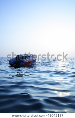 Motorized boat, blue sea and sun glare - stock photo
