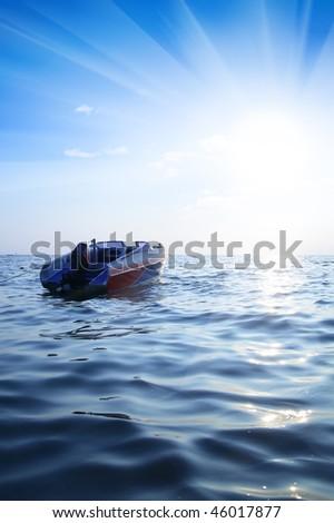 Motorized boat, blue sea and sun glare - stock photo
