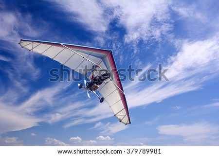 Motorizedr paraglider flying in the blue sky - stock photo