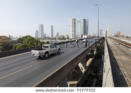 Motorway and elevated train rail traveling into Bangkok city across the Chao Phraya River with the urban modern city skyline in the horizon. - stock photo