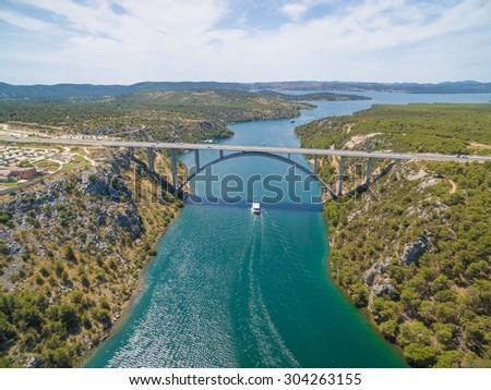 Motorway bridge over Krka river with boat sailing beneath, Croatia - stock photo
