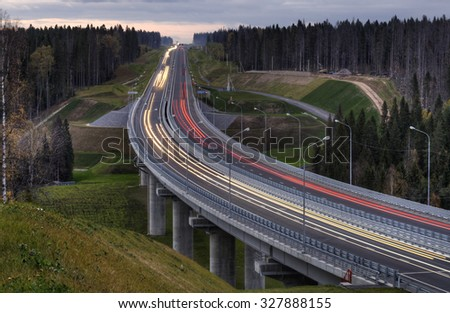 Motorway evening the Russian forest at dusk. - stock photo