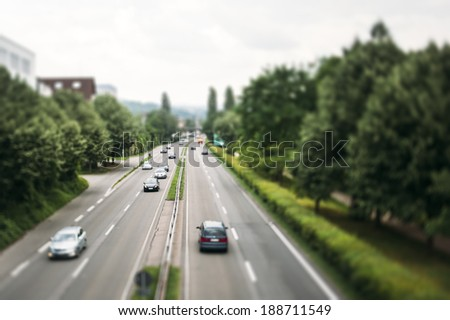 Motorway in Germany with speedy cars surrounded by green backgrounds - Tilt shift lens used to accent motorway and to emphasize the speed vision - stock photo