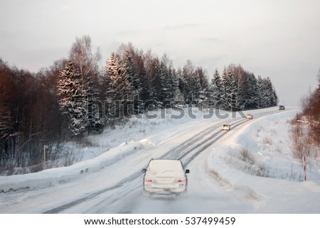 Motorway in the winter season. Snowfall and cars on the road
