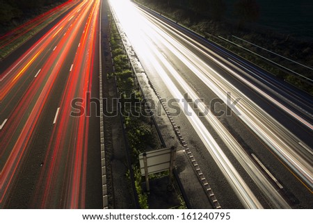 Motorway light trails heading towards manchester - stock photo