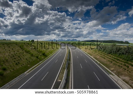 Motorway through fields with mountains on the background