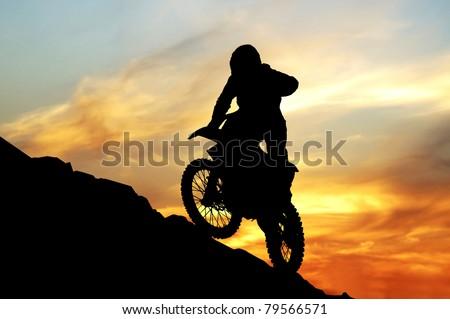 Mototsyklist to jump off a cliff - stock photo