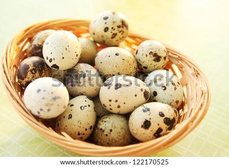 mottled fresh quail eggs in a basket - stock photo