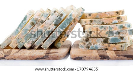 Mouldy bread on cutting board, isolated on white - stock photo