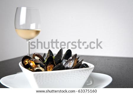 Moules marnieres (mussels) with a glass of white wine - stock photo