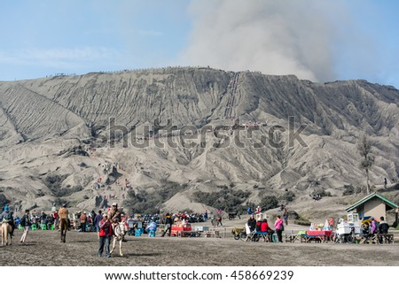 Mount. Bromo, East Java, Indonesia. May 21, 2016. Tourist hiking and climbing steps to Mount Bromo's crater at Bromo-Tengger-Semeru National Park, a protected nature reserve since 1919. - stock photo