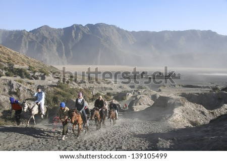 MOUNT BROMO, JAVA - SEPT 26: tourists on horses climbing the slopes of  mount bromo volcano on Sept 26 2007 in JAVA. The active Mount Bromo is one of the most visited tourist attractions in East Java, - stock photo