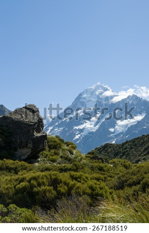 Mount Cook ahead, beyond the lush green valley and rock outcrops on the Hooker Track in the, South Island, New Zealand. Summer snow remains on the Mount Cook peak in the distance. - stock photo