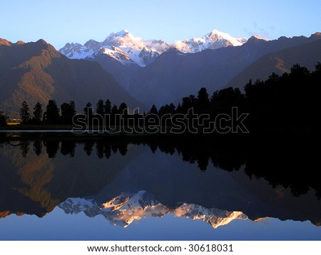 Mount Cook and Mount Tasman reflected in Lake Matheson at Sunset. New Zealand - stock photo