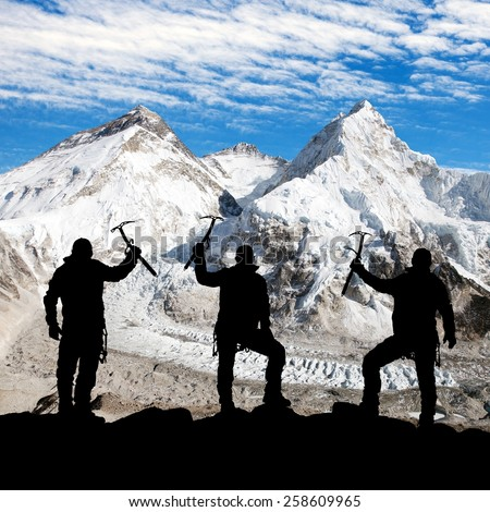 Mount Everest, Lhotse, Nuptse and icefall Khumbu from Pumo Ri base camp and silhouette of climbing men with ice axe in hand - trek to everest base camp - Nepal  - stock photo