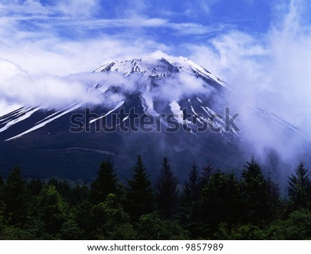Mount Fuji enshrouded in clouds - stock photo
