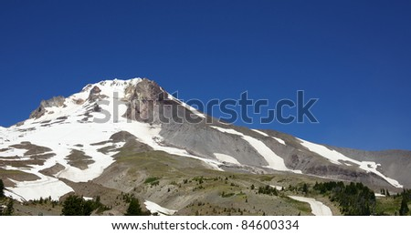 Mount Hood Peak with small glacier and snow against a dark blue sky - stock photo