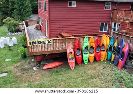 MOUNT INDEX ZONE, SEATTLE, WASHINGTON, USA - 19 AUGUST, 2015: Stack of multicolored kayaks on the rent shore in Mount Index. - stock photo