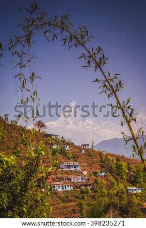 Mount Machhapuchhre and nepalese village on a slope of a mountain, Nepal - stock photo