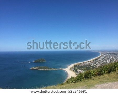Mount Maunganui and Main Beach crystal clear turquoise water in blue sky