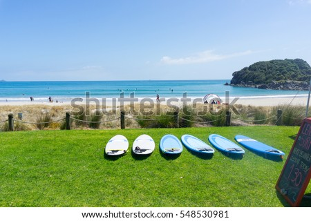MOUNT MAUNGANUI, NEW ZEALAND - DECEMBER 21; Mount Maunganui ocean-beach in summer and beach activities with hire surfboards lying on grass beach December 21, 2016, Mount Maunganui, New Zealand