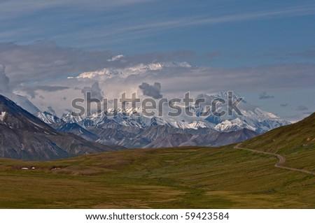 Mount McKinley peaks through dramatic clouds over lush green tundra in Denali National Park, Alaska. - stock photo