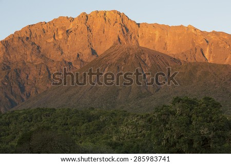 Mount Meru at sunrise near Arusha in Tanzania. Africa. Mt Meru is located 60 kilometres west of Mount Kilimanjaro. - stock photo