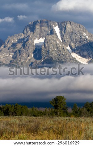 Mount Moran with a fogbank rising from the Snake River in Grand Teton National Park - stock photo