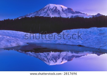 mount ranier reflection in snow bordered pond - stock photo