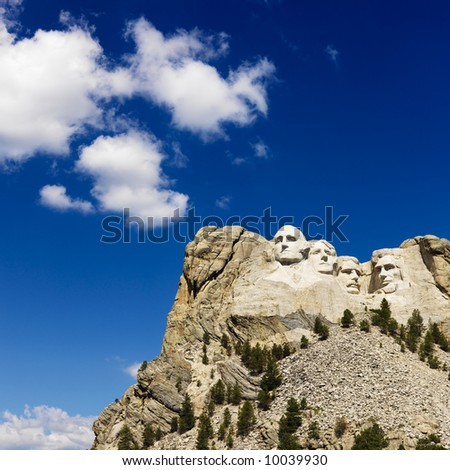 Mount Rushmore National Memorial with blue cloudy sky.
