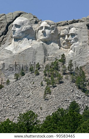 Mount Rushmore with the faces of former presidents George Washington, Thomas Jefferson, Theodore Roosevelt and Abraham Lincoln curved into it - stock photo