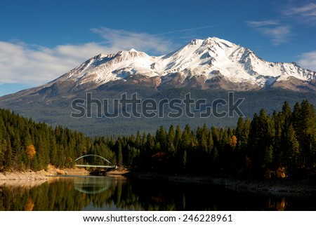 Mount Shasta standing above a lake with the name Siskiyou - stock photo
