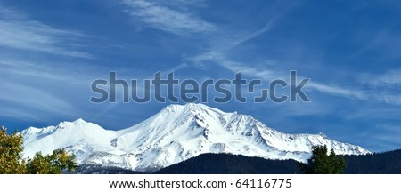Mount Shasta with a fresh coat of snow and wispy clouds - stock photo