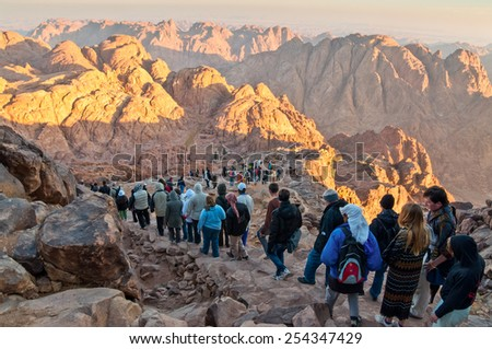 MOUNT SINAI, EGYPT - NOVEMBER 25: Pilgrims and tourists on the pathway from the Mount Sinai peak and panorama rocks of Mount Sinai in early morning at November 25, 2010.  - stock photo
