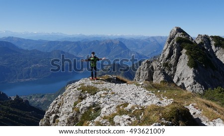 MOUNT SOUTHERN GRIGNA - ITALY - CIRCA OCTOBER 2016:  a hiker stands on the top of a slope on mount southern Grigna, Lombardy, Italy and admires the beauty of the panorama with lake Como and the Alps.