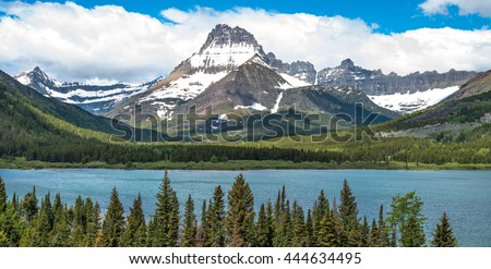 Mount Wilbur - A panoramic spring view of Mount Wilbur rising high at side of Swiftcurrent Lake  in Many Glacier region of Glacier National Park, Montana, USA. - stock photo
