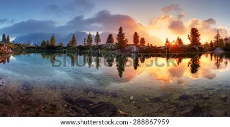 Mountain alps lake sunset panorama in Dolomites - stock photo