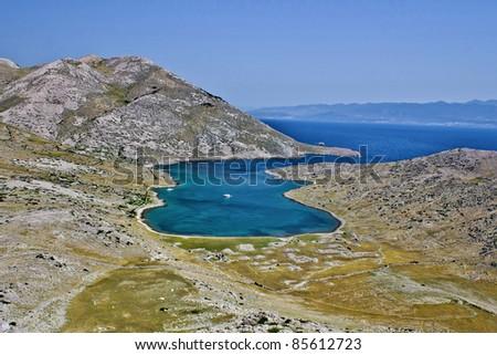 "Mountain and sea dream scape - ""Mala Luka"", Island of Krk, Croatia, with ancient ruins of Corinthia - stock photo"