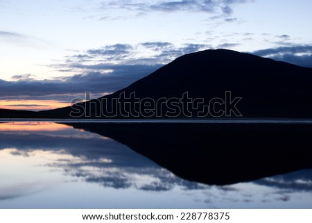 Mountain and sky reflected in tidal lake, Scotland - stock photo