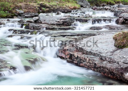 Mountain beautiful river cascade with flowing clear water from the tops - stock photo