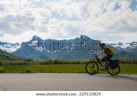 Mountain bike cyclist at sphalt road, Lofoten, Norway - stock photo