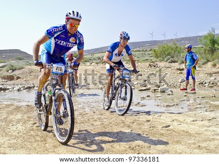 """mountain bike cyclist competing in a race through the nature park dessert """"Las Bardenas"""". Temperature reaches 37ºc on June 28th, 2008, in Tudela, Navarre, Spain. BARDENAS REALES, NAVARRE, SPAIN - stock photo"""