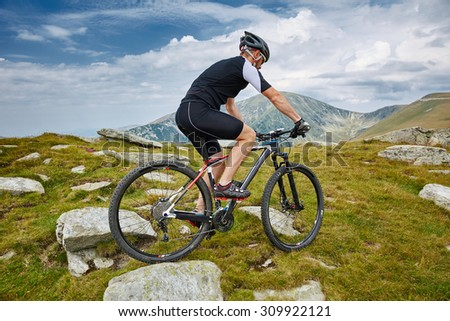 Mountain bike cyclist in sport equipment and helmet riding on rugged trails - stock photo
