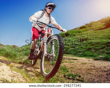 Mountain bike. Cyclist rides a bicycle down. Downhill sports. - stock photo