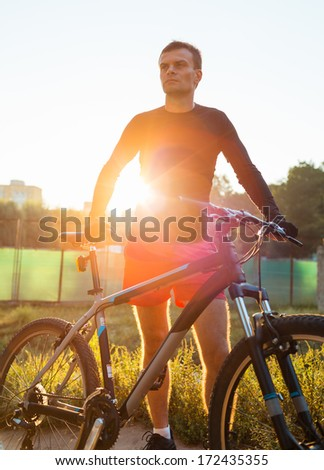 Mountain bike cyclist riding at sunrise healthy lifestyle active athlete doing sport - stock photo