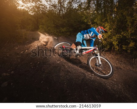 Mountain Bike cyclist riding forest track at sunrise healthy lifestyle active athlete. Downhill biking. - stock photo