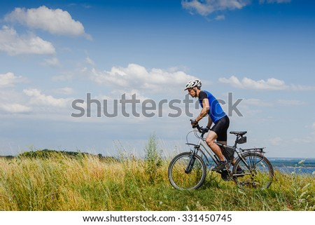 Mountain Bike cyclist riding Meadow track on sunny day. healthy lifestyle active athlete  - stock photo