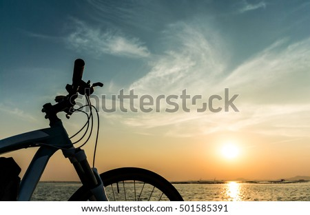 Mountain bike parking at jetty with sea and sunset sky background